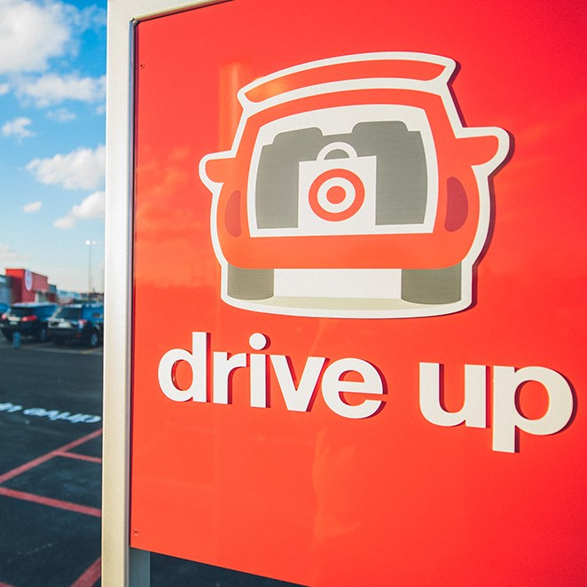 "In a parking lot, a red sign with a car icon reading ""drive up"" is in the foreground.  In the background, a grey building with a red store entrance."