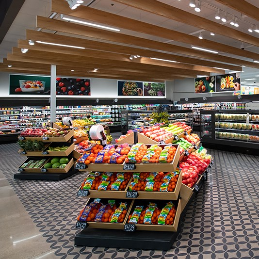 Shelves of food product set on a concrete floor with a dark stencil pattern. In the background, coolers filled with fresh foods.