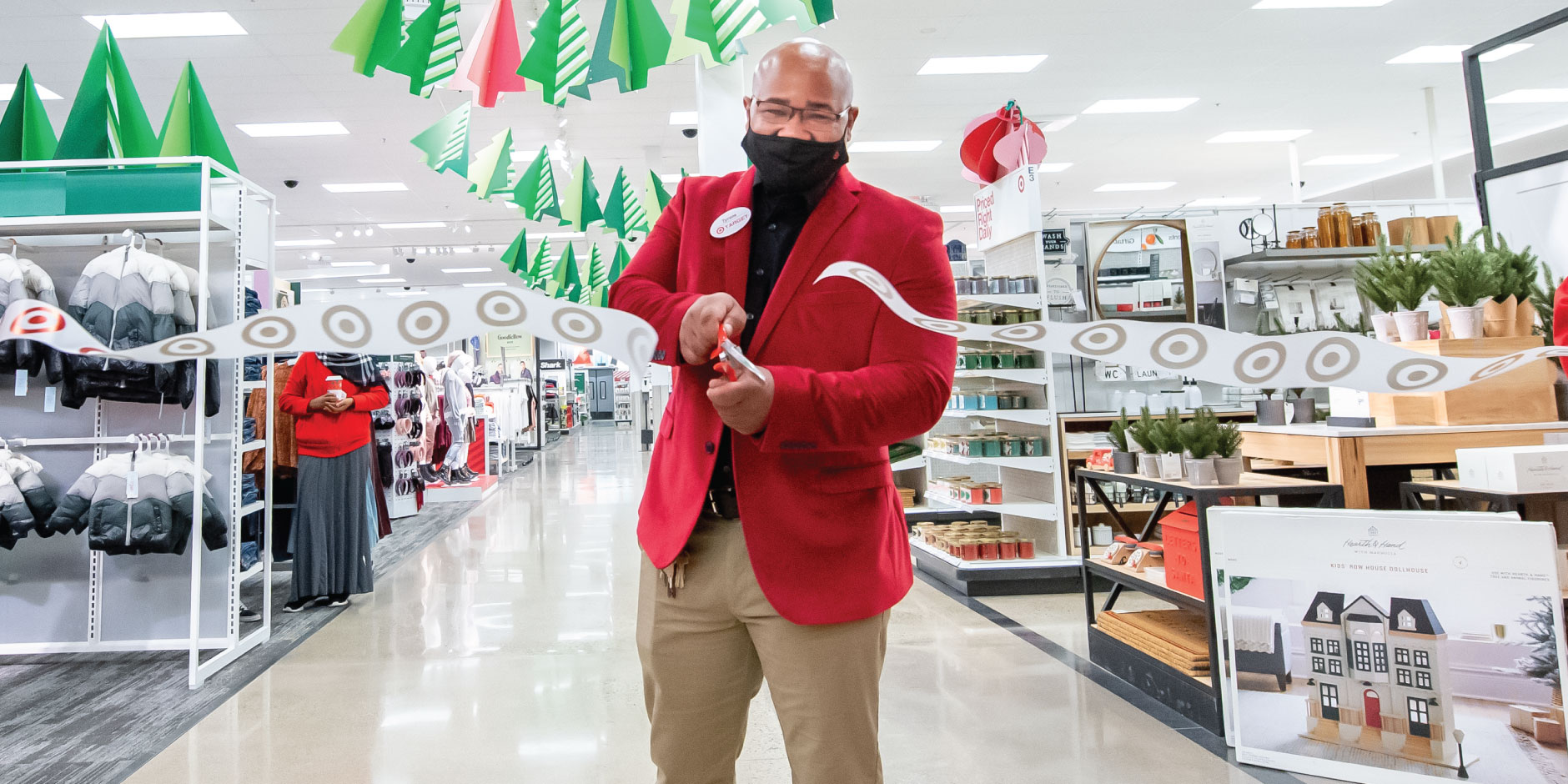 A target team member cuts a white ribbon that is covered in red Target bullseye logos. In the background, shelves of product.