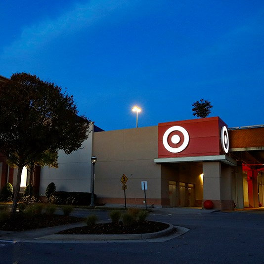 The exterior of the Target Buckhead store at night. A brown building with a red sign with the Target bullseye logo below an early evening sky. A small cluster of trees is in the foreground.