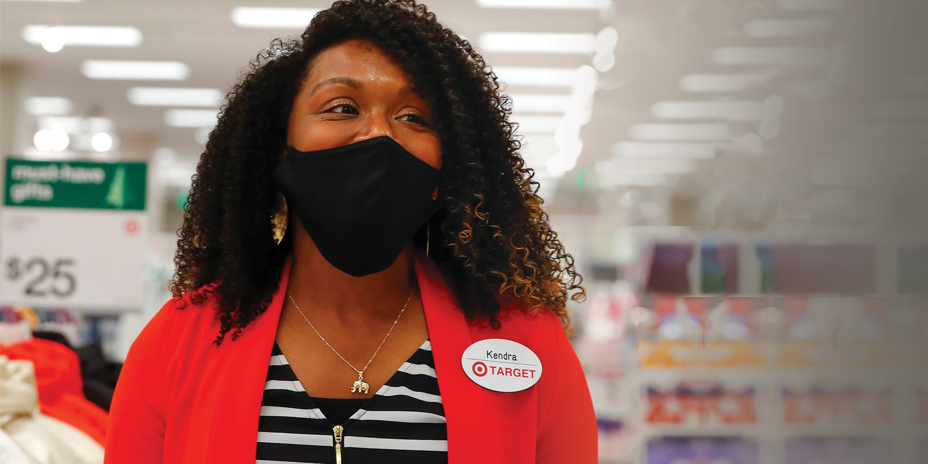 A Target team member in a red sweater and black face mask