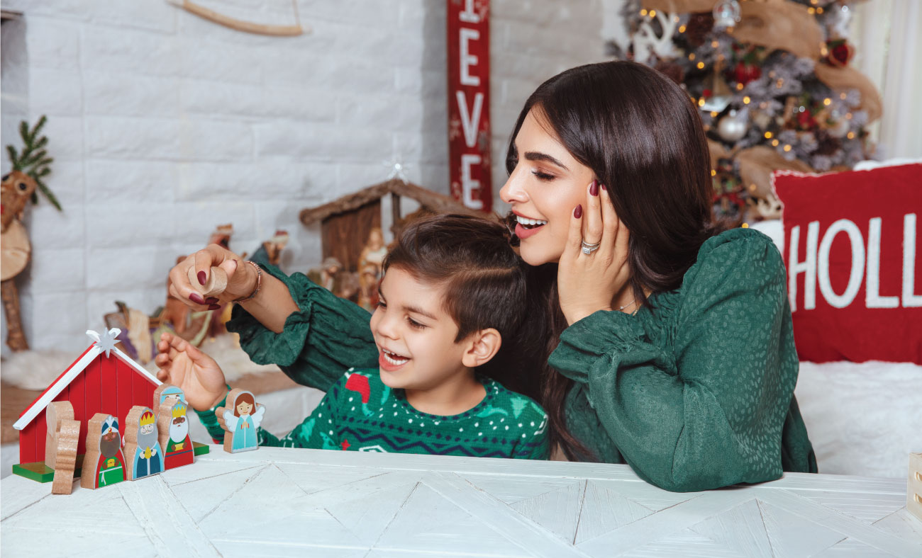 Alejandra and her son play with a wooden manger scene.
