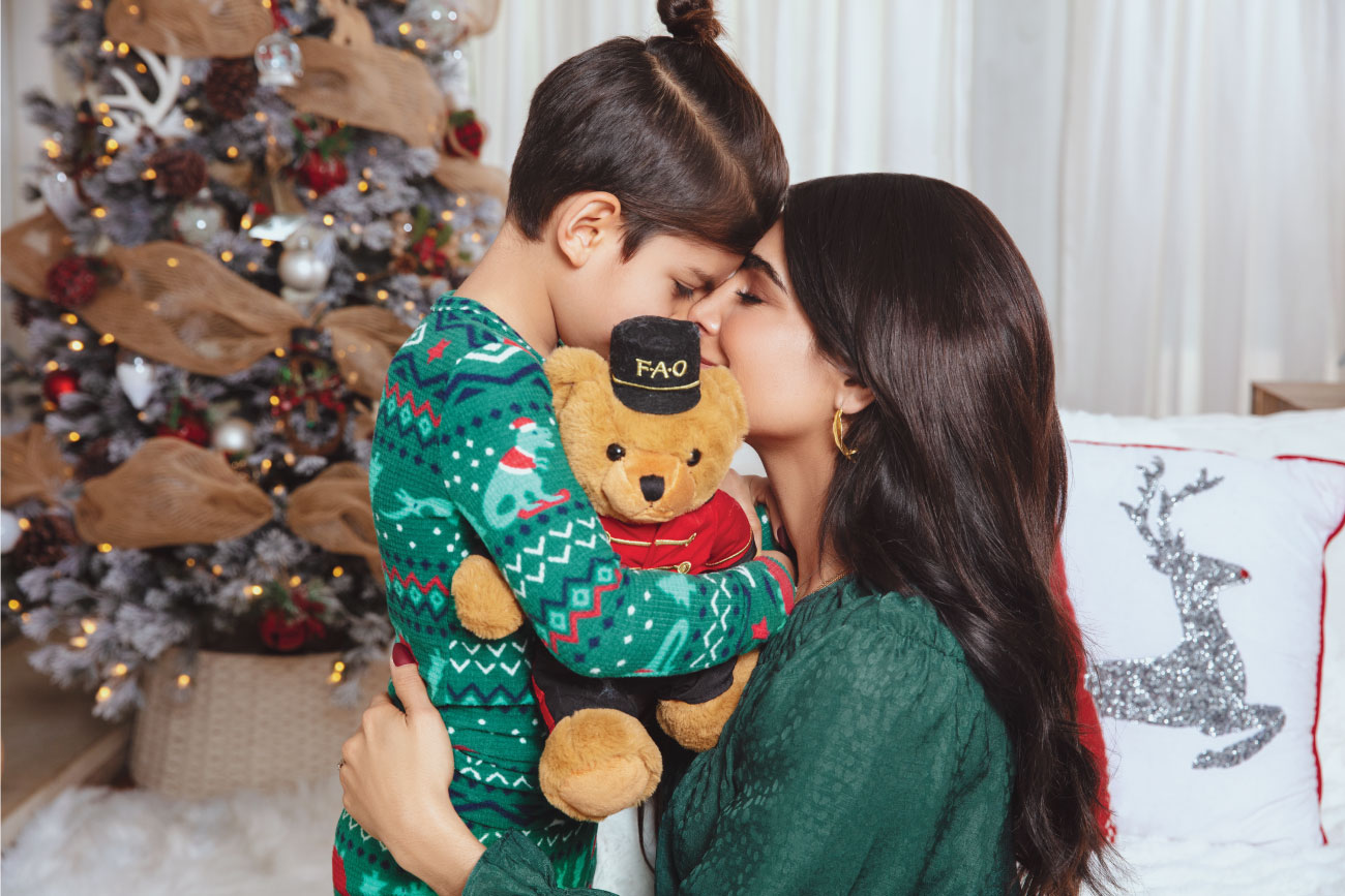Alejandra hugs her son as he snuggles a teddy bear dressed as a toy soldier