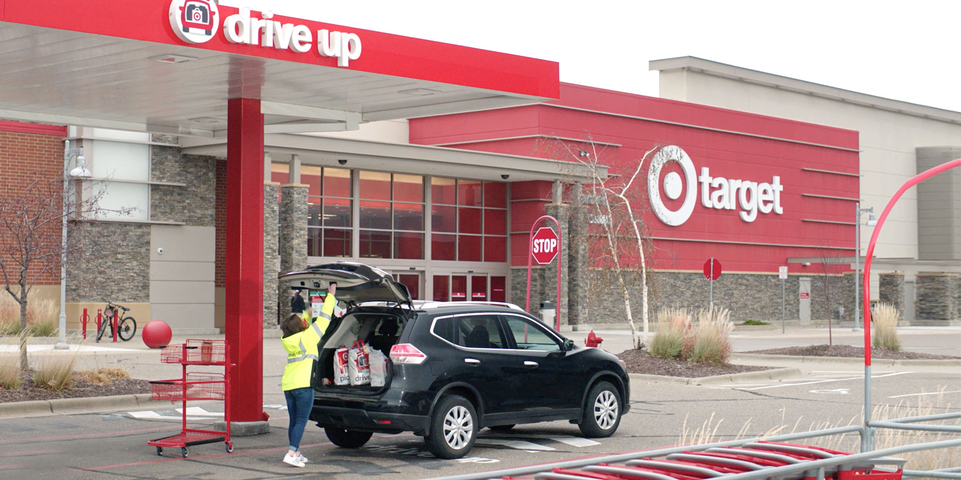 "A Target team member loads bags into the back of a SUV under a canopy with a sign reading ""drive up."" In the background, a Target store."