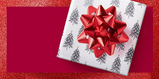 A red shiny bow on top of a square box covered in wrapping paper on a red background.