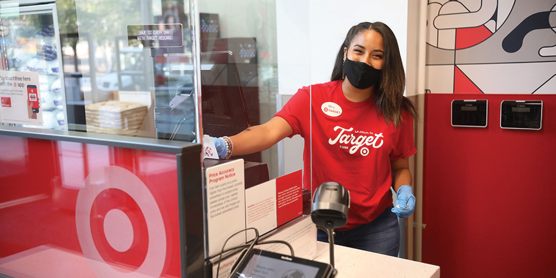 A team member in mask, gloves and red T-shirt smiles at a guest services counter in a Target store