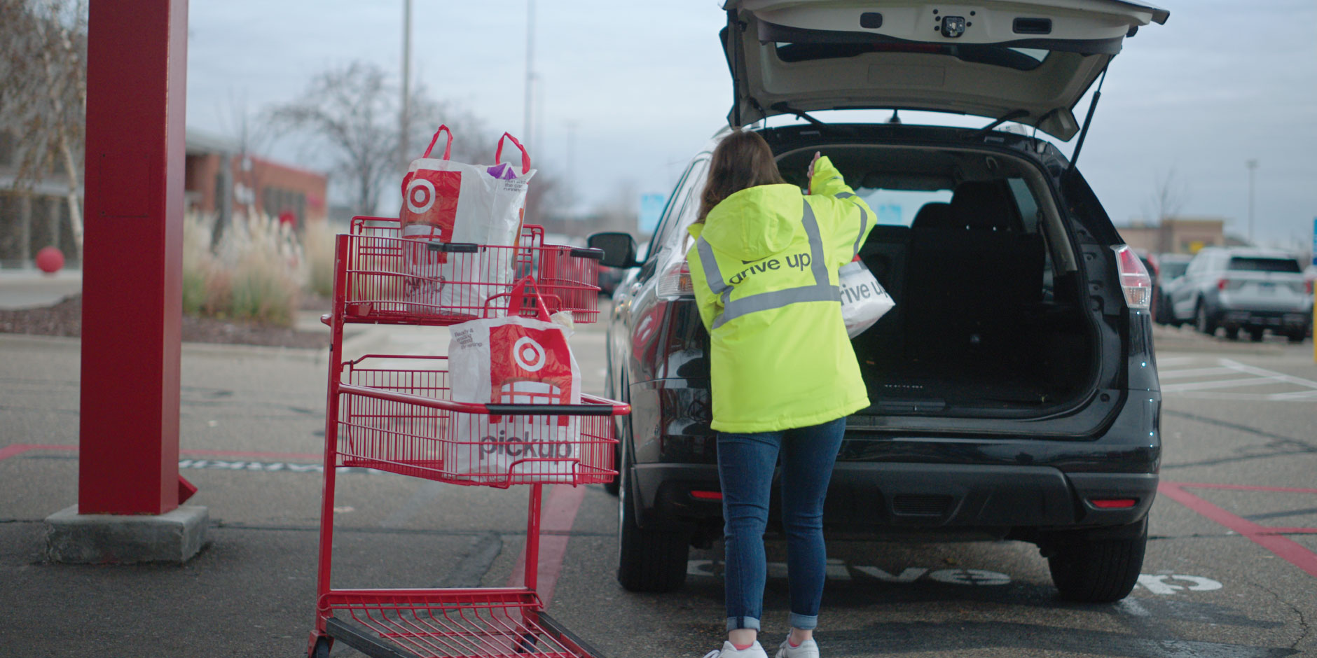 A team member in a yellow Drive Up vest places a package into the back of a guests' car
