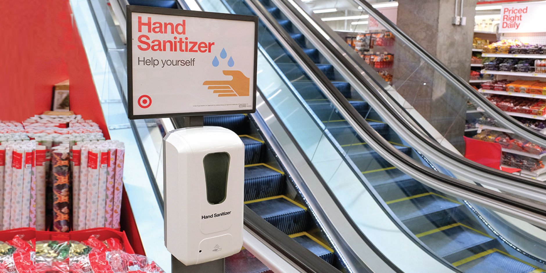 A hand sanitizing station is shown in a Target store with escalators in the background