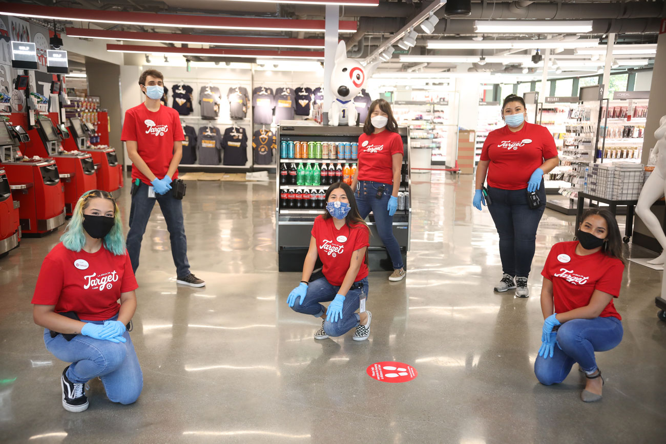 Target team members in matching red shirts and masks and gloves pose for a socially-distant photo
