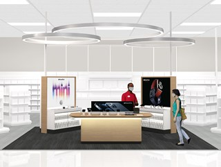 An illustration of the upcoming Apple destination in Target stores, which shows displays of electronics products and a team member assisting a guest at a counter. Both are wearing masks.