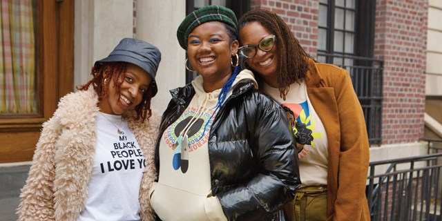 Three women pose in shirts from Target's Black History Month collection