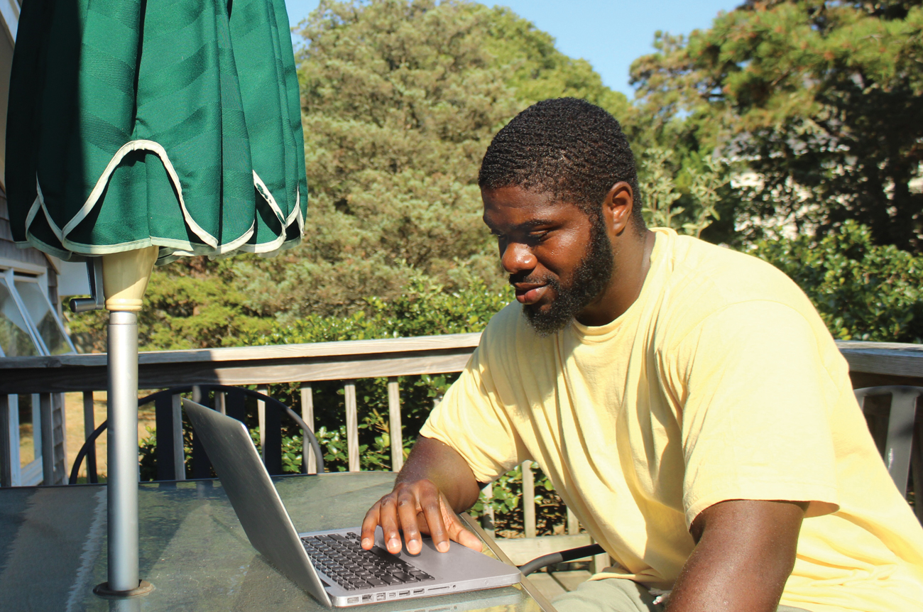 Isaiah sits on a deck oustide with his laptop.