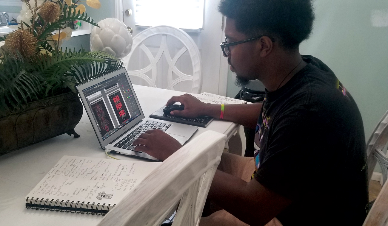 KeShawn sits at a table and works on his design at his laptop.