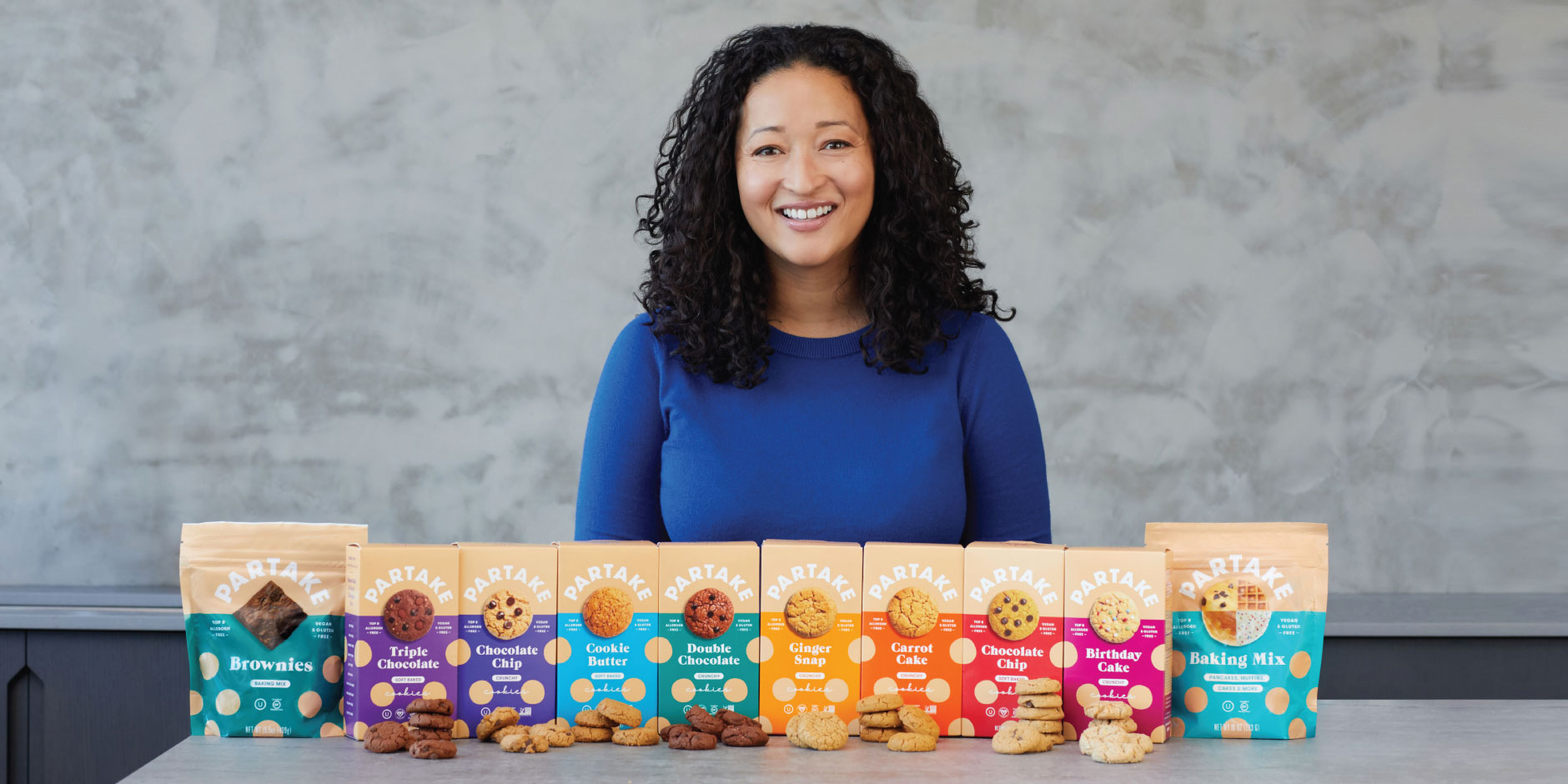 "A woman smiles and stands behind boxes of cookies labeled ""Partake"" displayed on a table."
