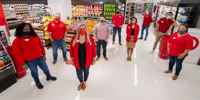 A group of team members in red with masks and name badges stand in an aisle at their Target store.