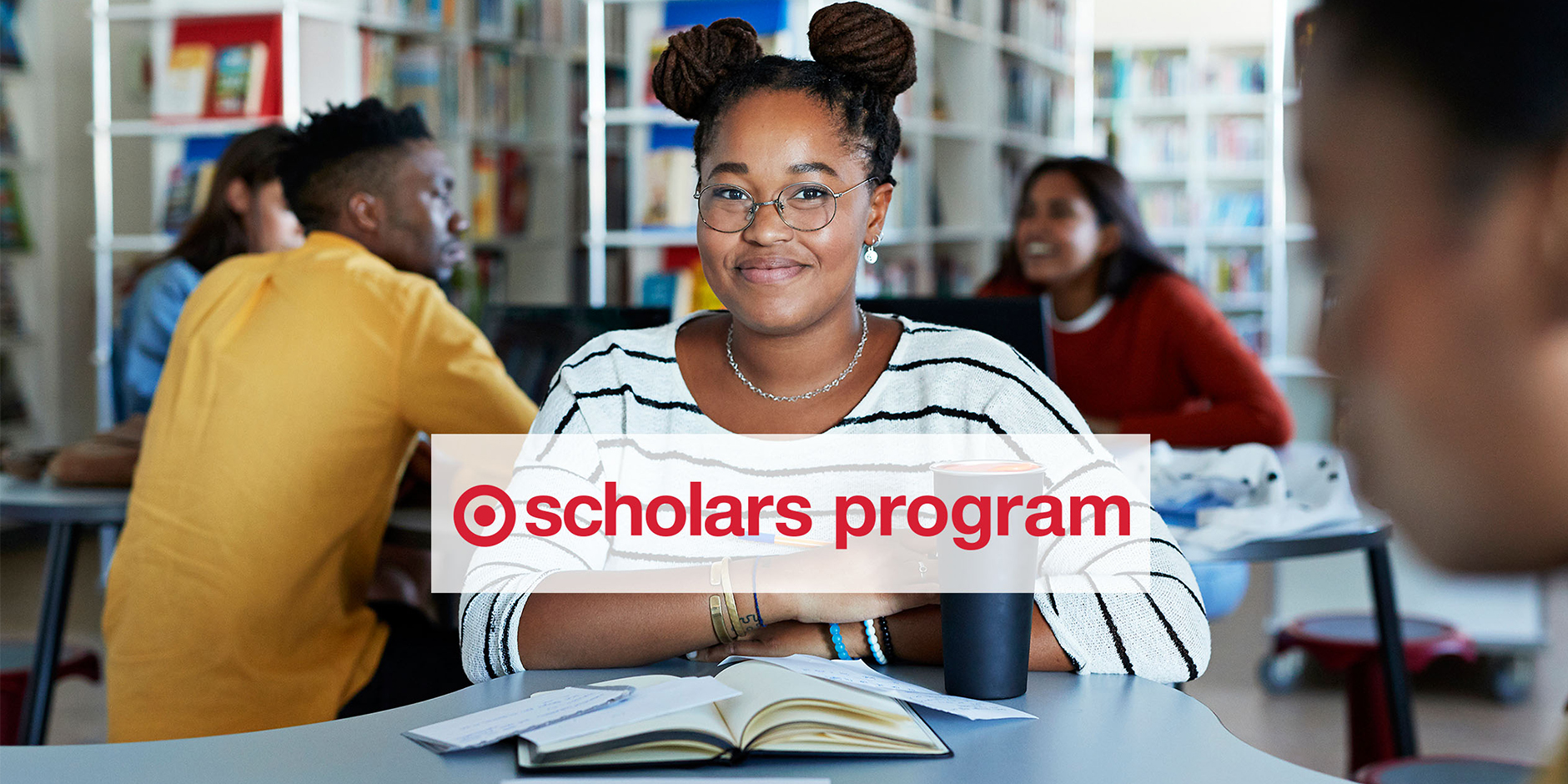 A smiling student in a striped shirt sits at a desk with her books while other students study in the background. A banner reads Target Scholars Program in red text over a white background.