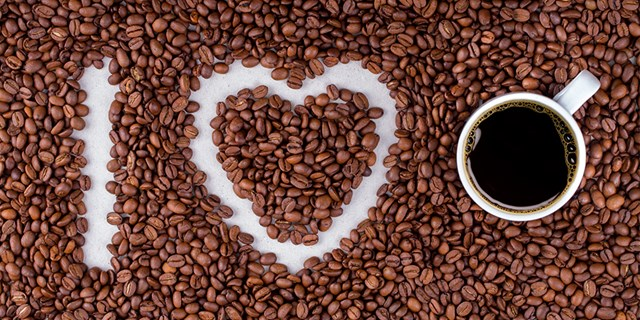 coffee beans that spell out I heart you with a cup of brewed coffee
