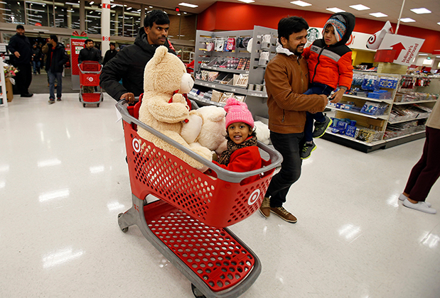 A family pushes a cart through the Target entrance, with a kid and two plush bears in the basket
