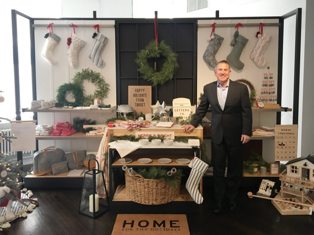 Brian Cornell stands in front of a display table with holiday decor, stockings, dishes and more
