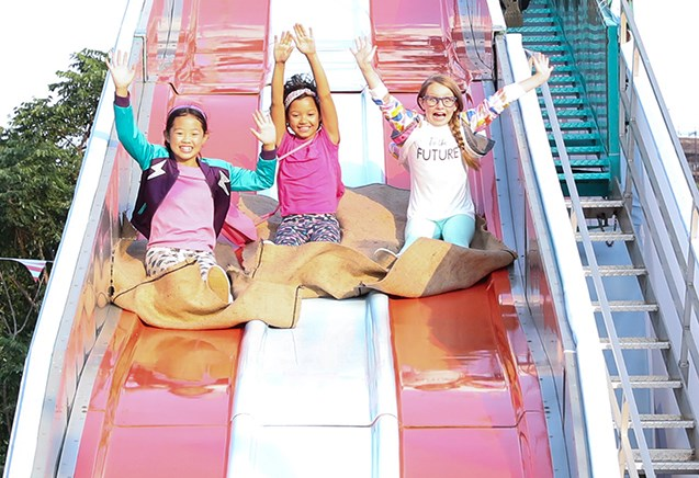 Three kids with their hands in the air as they slide down on a giant slide