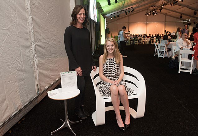 Claire sitting in her chair with her mentor at the Teen Design Fair event.