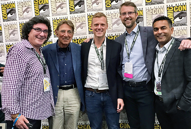 The five attendees with badges around their necks, standing in front of a Comic Con press background