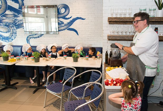 Kids look on as Chef Jamie gets ready to blend a smoothie.