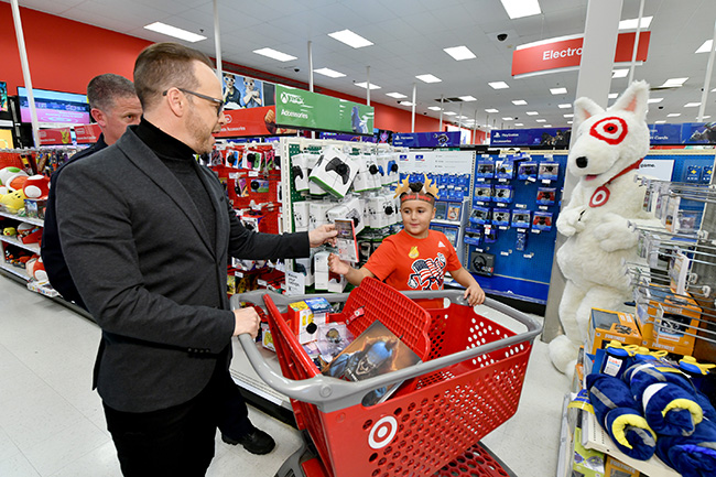 Donnie Wahlberg hands a video game to a young boy from a red shopping cart as Bullseye looks on