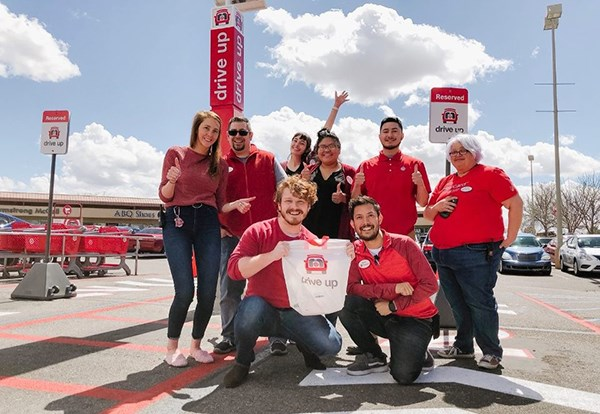 eight team members pose in front of Drive Up area in parking lot with red shirts and jeans