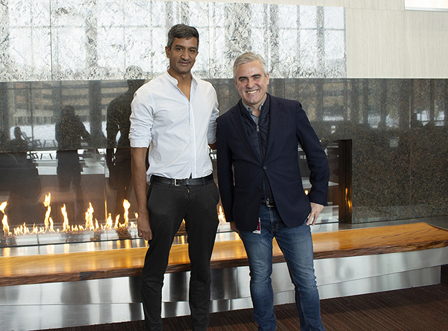 Ramesh stands next to Mike in front of a stone fireplace and wooden bench