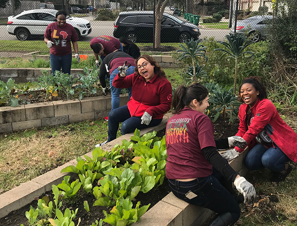 Seven team members wearing red shirts stop to wave as they volunteer in a neighborhood garden