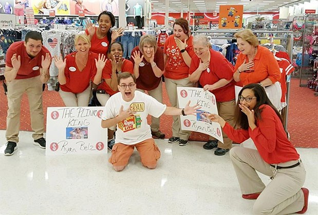 Ryan kneels on the floor at his Target store surrounded by his co-workers holding signs and cheering
