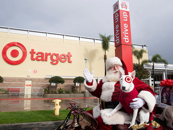 Santa and Bullseye the dog smile while sitting in a sleigh full of gifts in front of a Target store