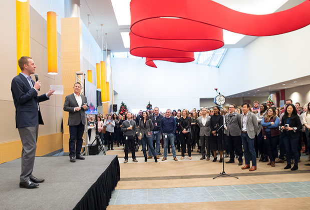 Bill Smith stands on stage with Brian Cornell at Target headquarters speaking to a crowd