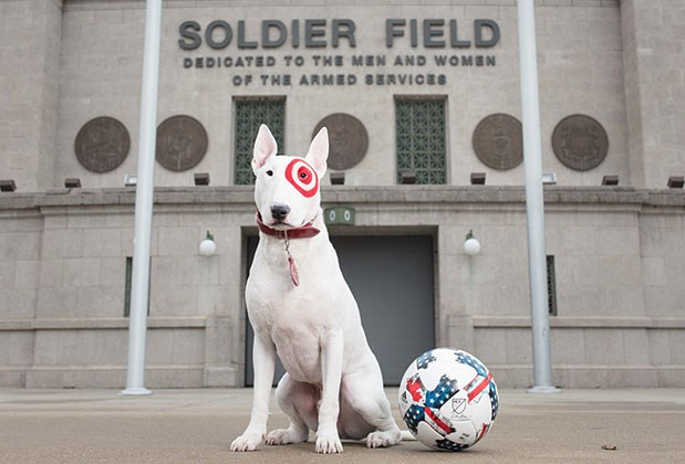Bullseye stands next to a soccer ball in front of Chicago's Soldier Field