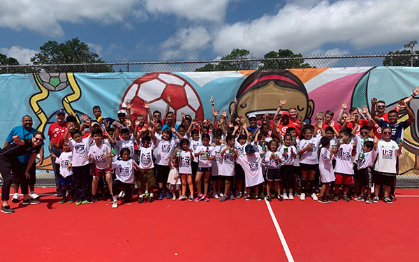 A large group of kid soccer players and Target team members cheer on the new pitch