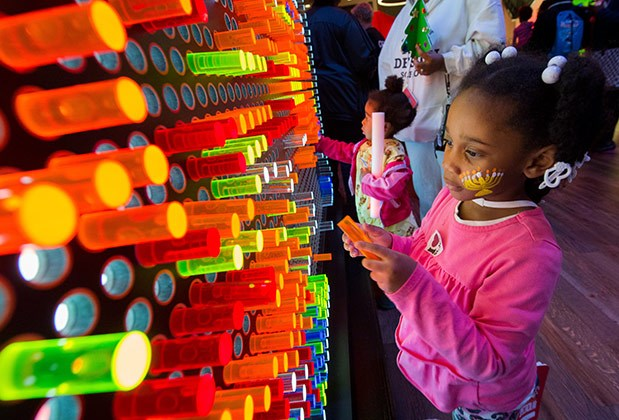 A little girl adds a peg to the illuminated light board at Target's Bullseye's Bash event