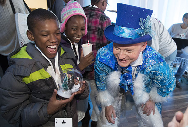A performer in a blue top hat watches a card trick with two kids holding a snow globe