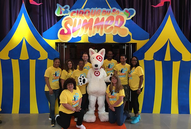 Nine volunteers and our Bullseye the dog mascot pose in front of a blue and yellow big top display