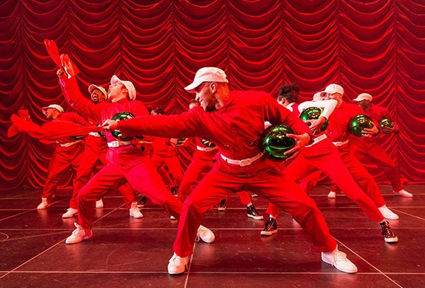 Dancers in red jumpsuits holding shiny green bulbs perform onstage