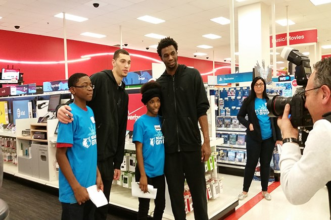 Zach LaVine and Andrew Wiggins pose with kids in front of the Electronics department.