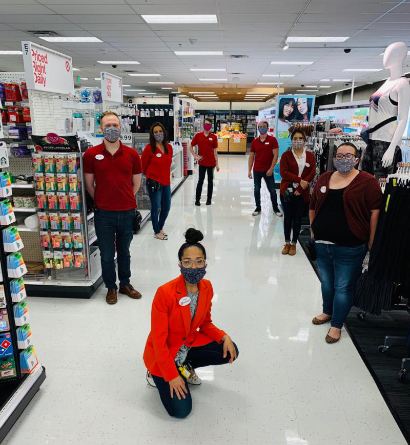 Seven team members stand six feet apart from each other in a Target aisle, wearing masks