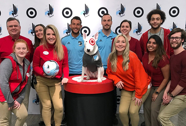 Team members stand with Bullseye the dog and two MLS players