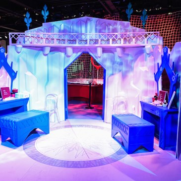 An ice castle-themed frozen view of a blue room in Target Wonderland with blue benches, a blue dress