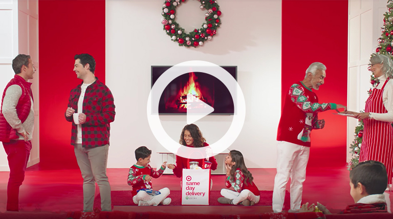 Family and friends dressed in red gather around a wreath-bedecked fireplace. A woman and two kids peek into a Same Day Delivery bag.