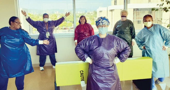six medical professionals in plastic gowns and masks