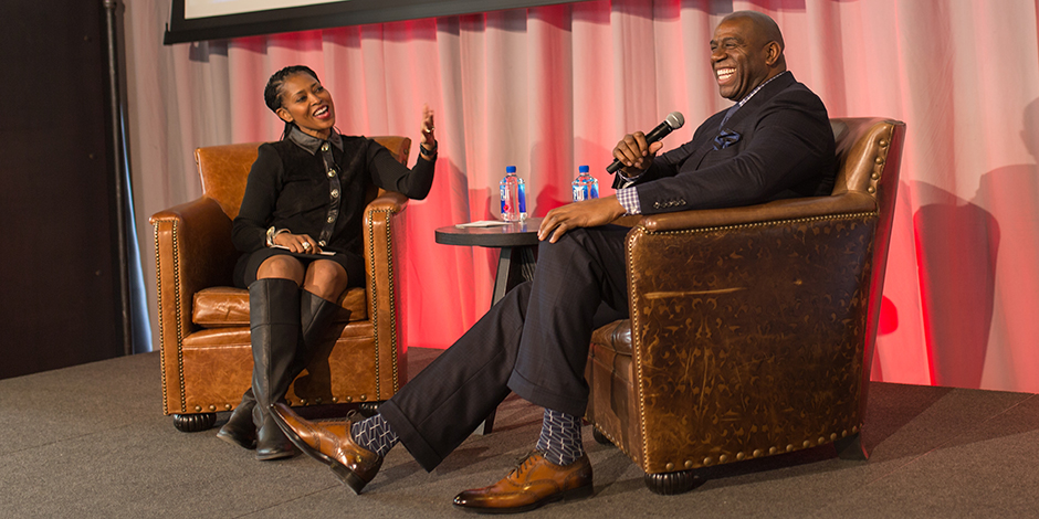 Laysha Ward and Magic Johnson (to her right) sitting in chairs onstage at the Outer Spaces event.